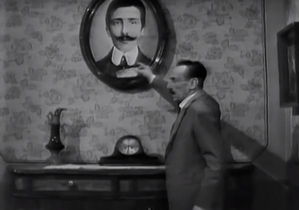 """E. De Filippo sventola il biglietto vincente davanti all'immagine del padre defunto (immagine tratta dalla commedia """"Non ti pago"""", 1964)."""