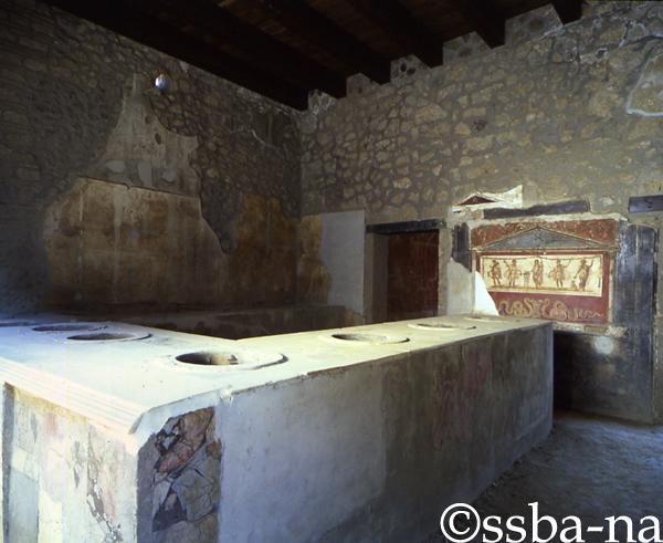 Pompei, Termopolio di L. Vetutius Placidus. Il larario e parte del bancone con i contenitori per cibi e bevande: in uno di essi si rinvenne un gruzzolo di monete. SSBANP/AF, Dia 35742