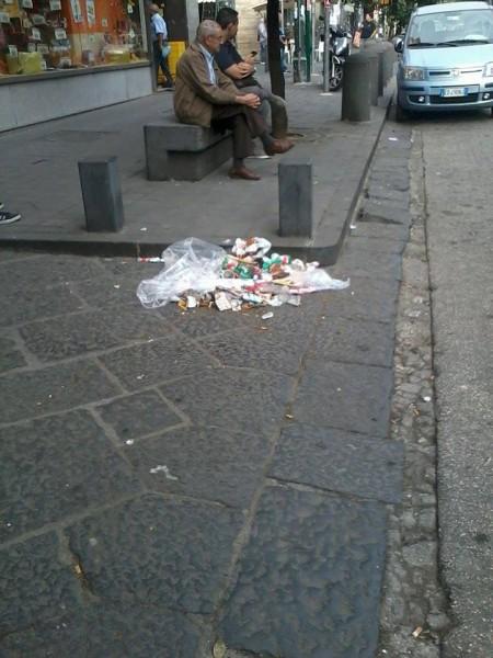 Spazzatura ammucchiata e non raccolta lungo il ciglio di un marciapiede al corso Secondigliano.